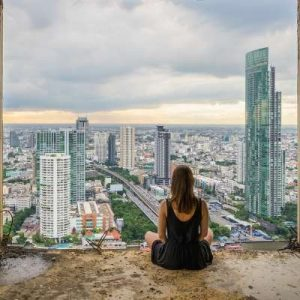 Lady meditating with city view